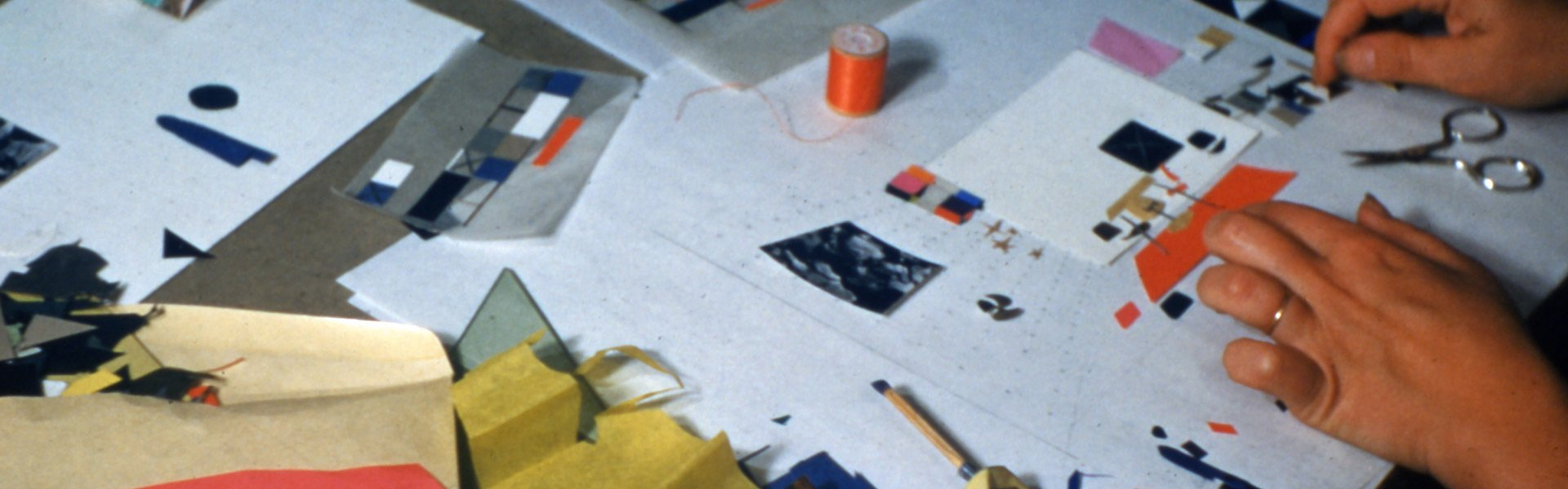 A close up of Ray Eames's hands as she works through a new design on paper